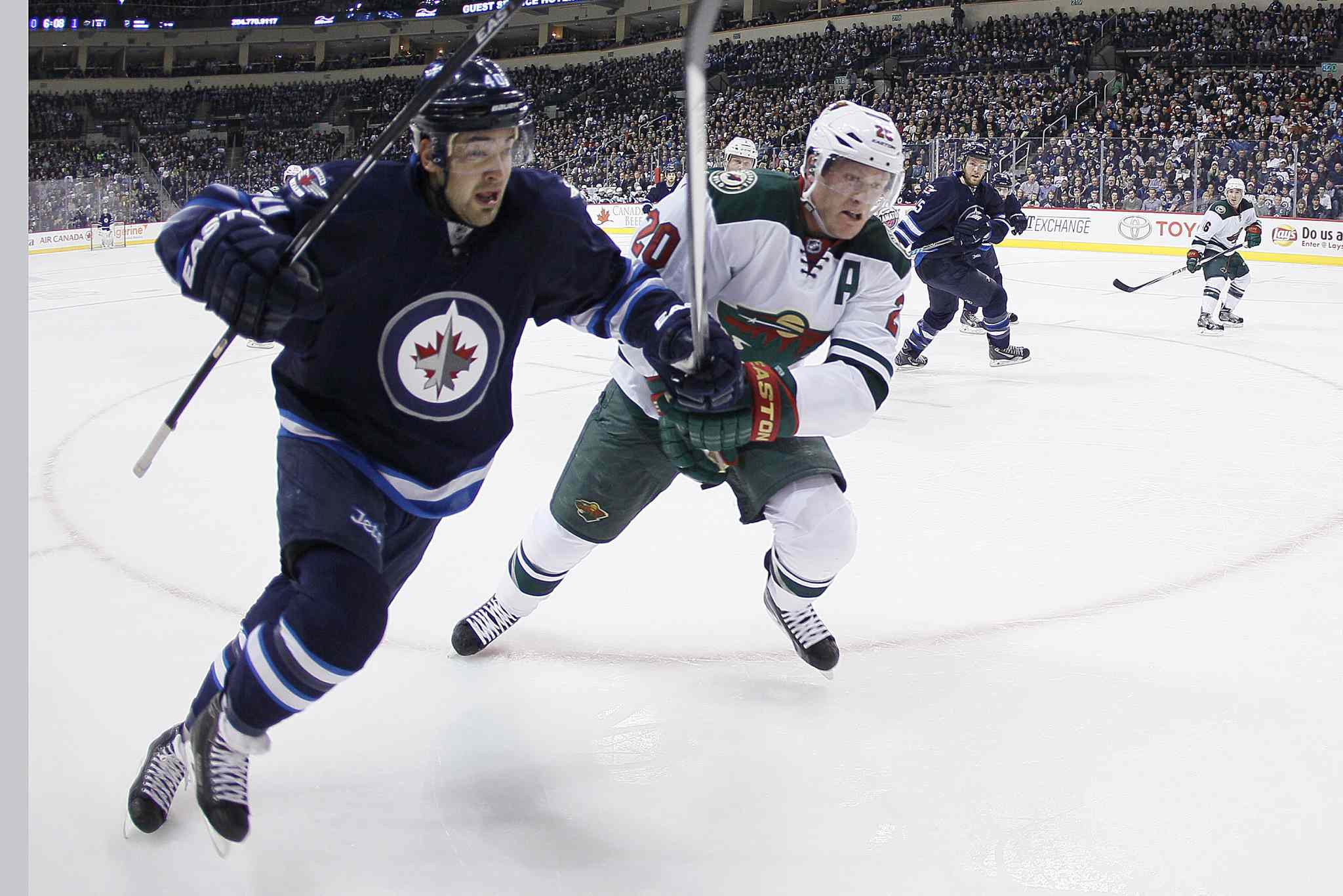 Jets forward Devin Setoguchi and Wild defenceman Ryan Suter drive for the puck in the corner during the second period.