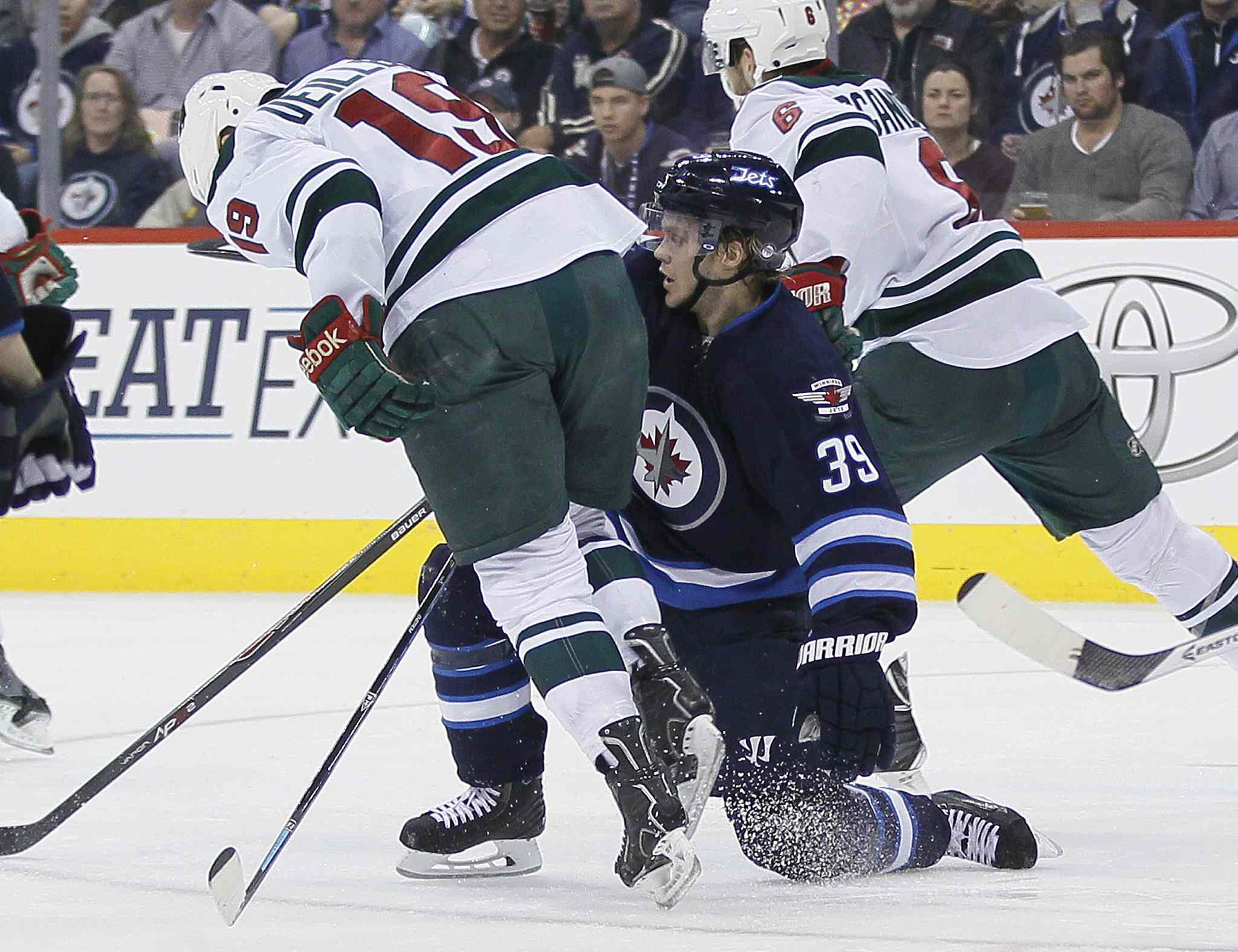 Minnesota's Stephane Veilleux gets checked by Jets defenceman Tobias Enstrom during second-period play.