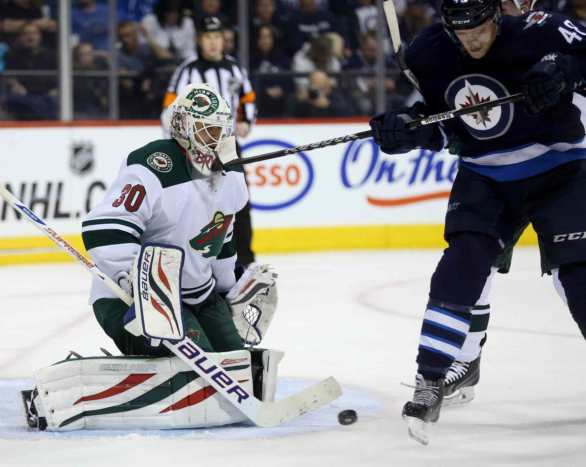The Wild's Ilya Bryzgalov takes a stick to the mask from the Jets' Carl Klingberg during the second period.