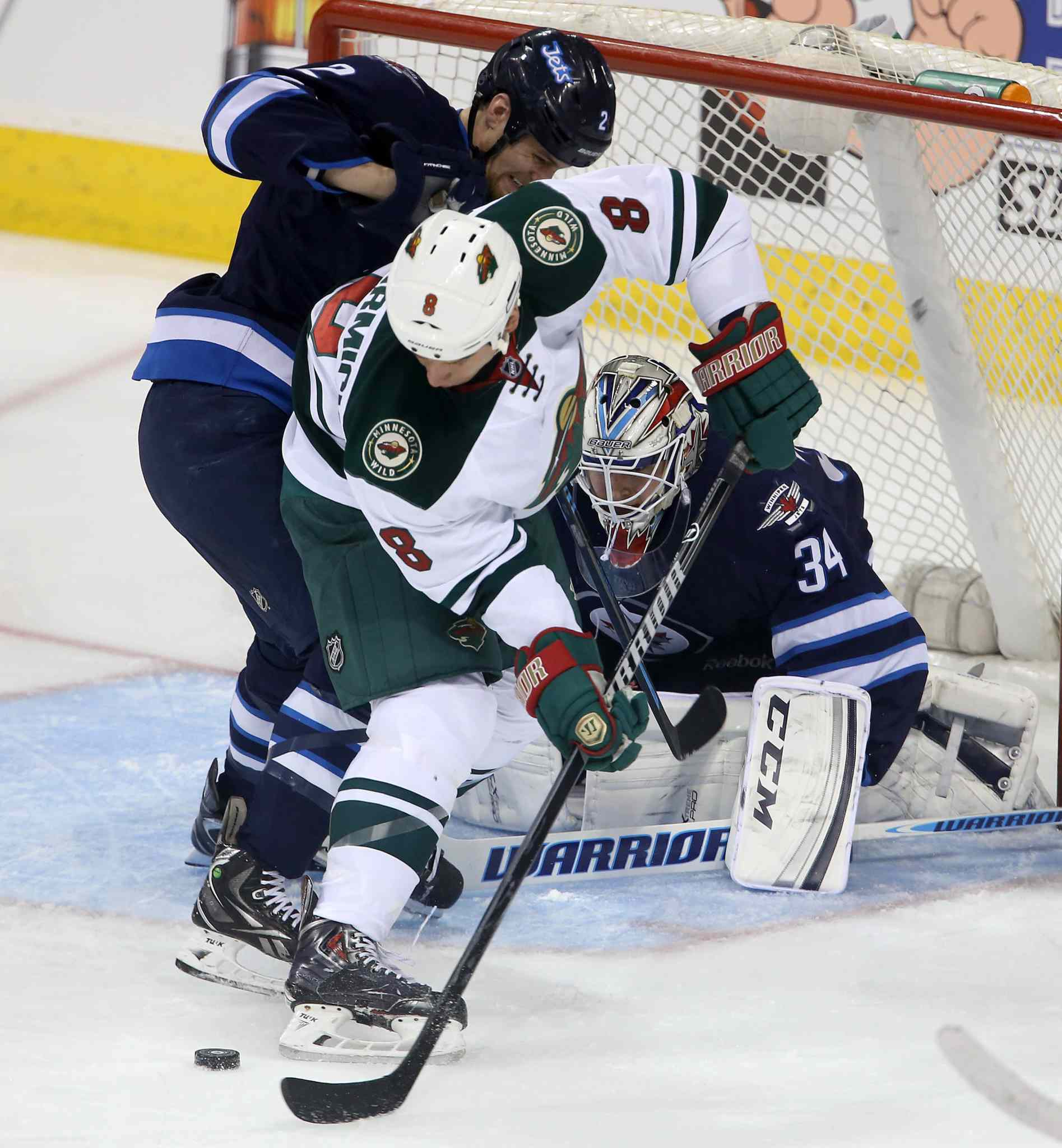 Jets defenceman Adam Pardy battles with the Wild's Cody McCormick in front of Jets goaltender Michael Hutchinson during the first period.