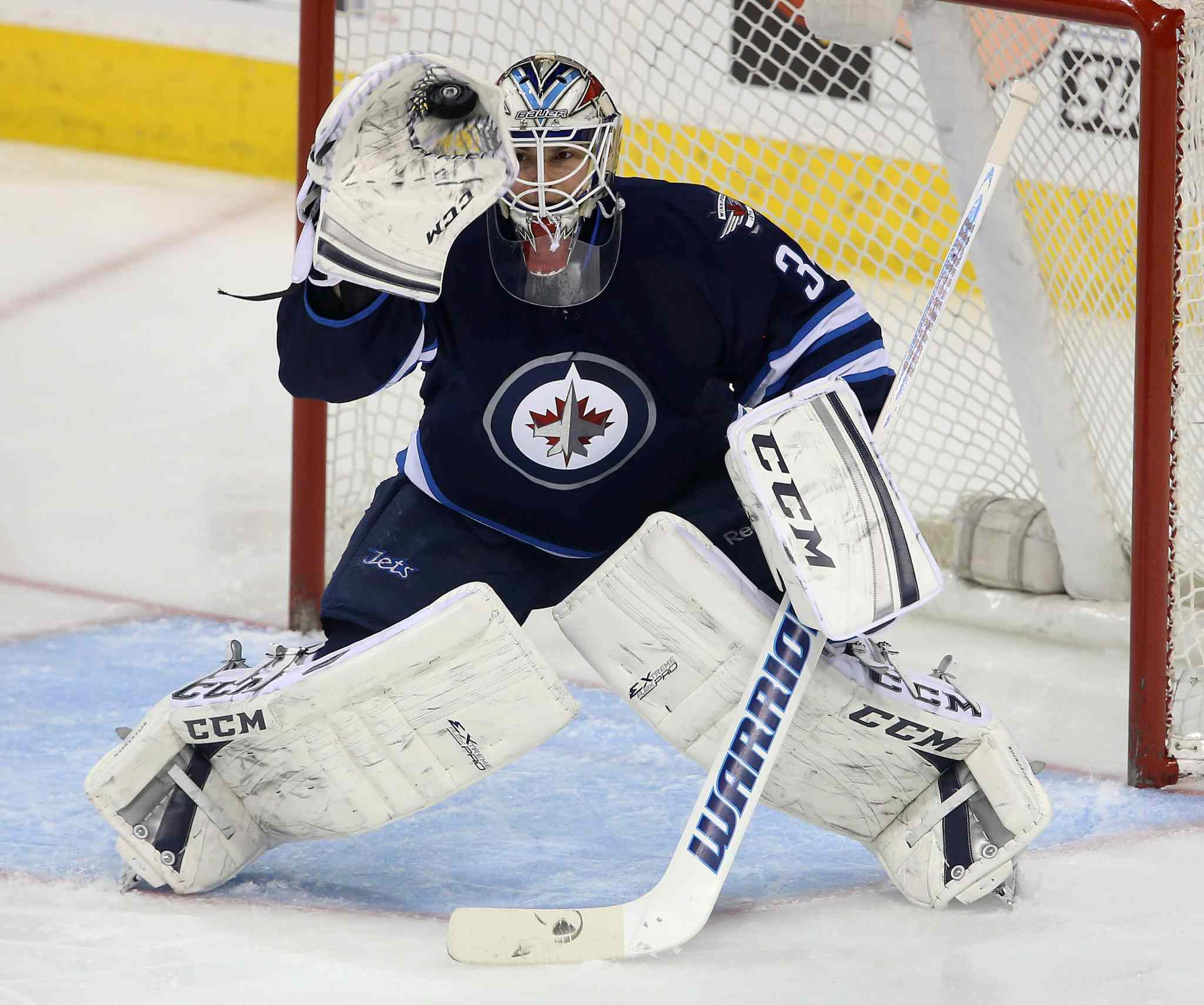 In his first NHL start, Jets goaltender Michael Hutchinson makes a glove save against the Minnesota Wild during the first period.