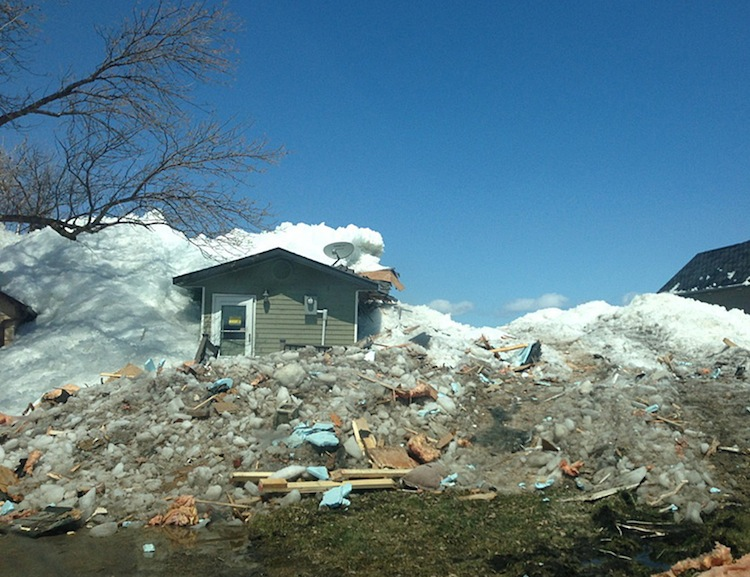 A home is partially buried in ice and debris litters the ground.