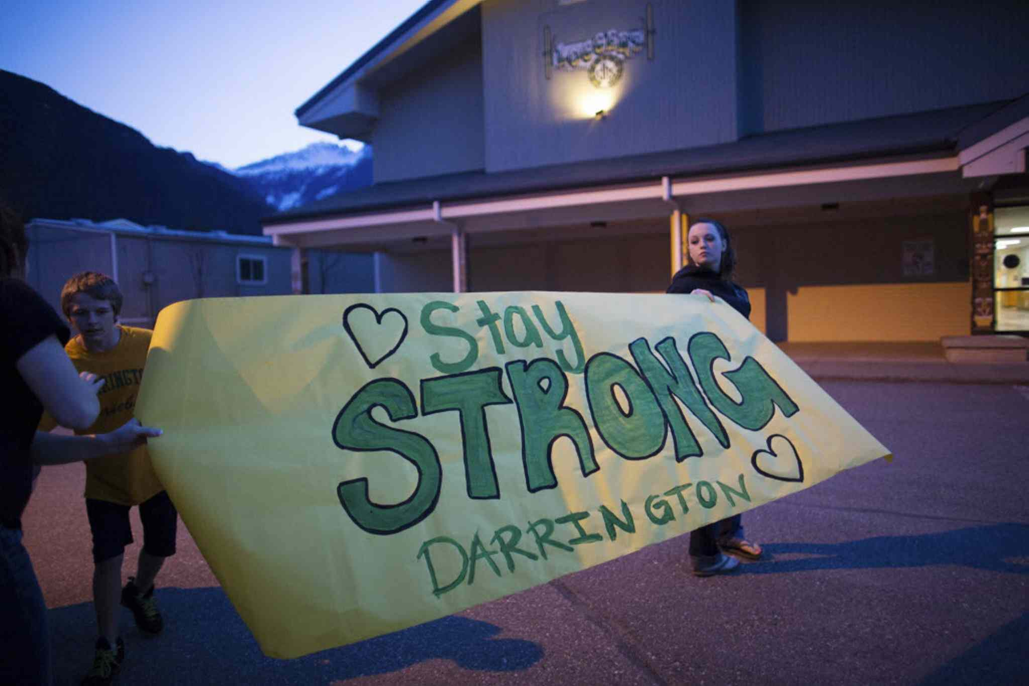 Shelby Stafford, 14, and Hailey Hudson, 17, hold a banner they made at Darrington High School in the wake of Saturday's mudslide in Snohomish County.