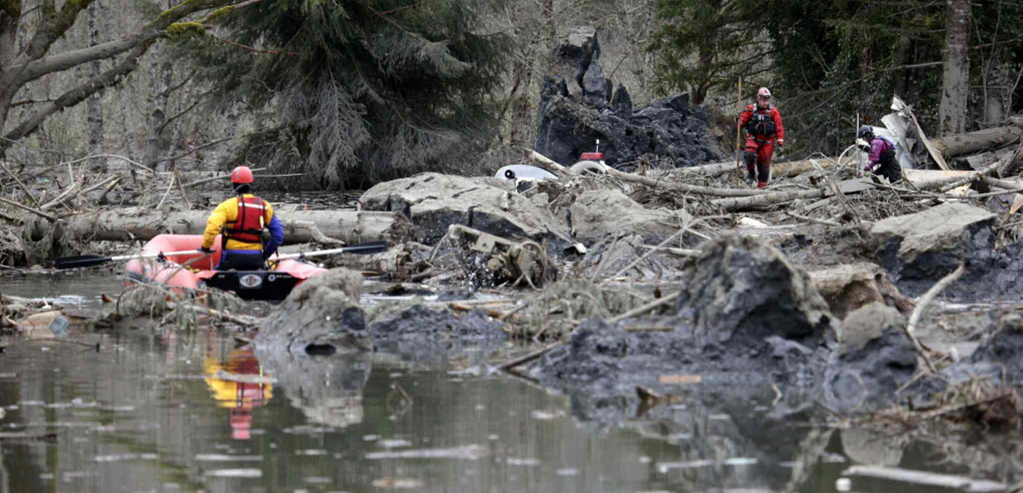 Searchers on water and land look through debris following the mudslide in Oso, Wash.