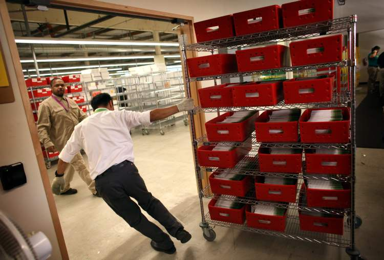 Ballots are moved in the King County Elections ballot processing facility in Renton, Wash. as the mail-in ballots continue to come in on Election Day, Tuesday. (Joshua Trujillo / The Associated Press)