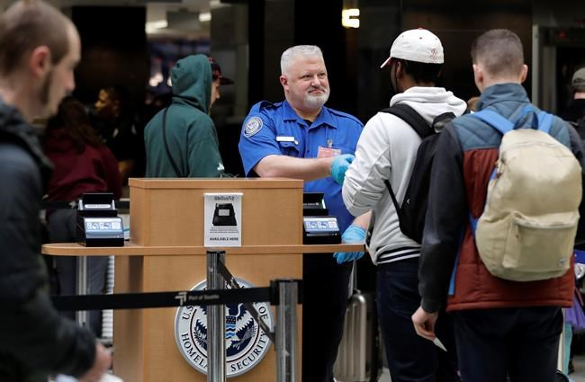 A TSA worker checks hands an identification card back to a traveler, Friday, Jan. 25, 2019, at Seattle-Tacoma International Airport in Seattle. Yielding to mounting pressure and growing disruption, President Donald Trump and congressional leaders on Friday reached a short-term deal to reopen the government for three weeks while negotiations continue over the president's demands for money to build his long-promised wall at the U.S.-Mexico border. (AP Photo/Ted S. Warren)