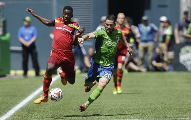 FILE - In this May 31, 2014, file photo, Seattle Sounders' Zach Scott (20) and Real Salt Lake's Olmes Garcia, left, get airborne as they chase down a ball along the sideline during an MLS soccer match in Seattle. As the MLS grows, there remains a significant economic gap among player salaries. Scott, who has started 67 MLS regular season games in his six seasons, has never made more than $52,500 per season. (AP Photo/Ted S. Warren)