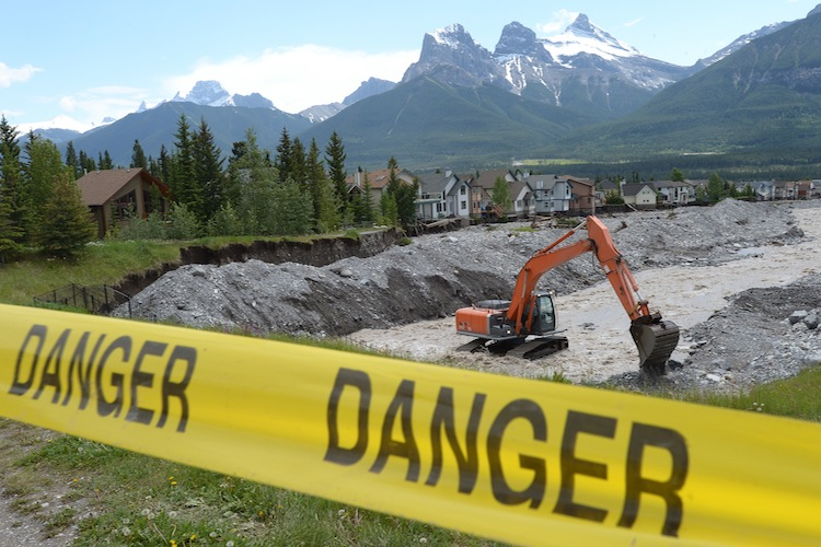 Excavators work on the Cougar Creek bed two days after it tore through Canmore, Alta.
