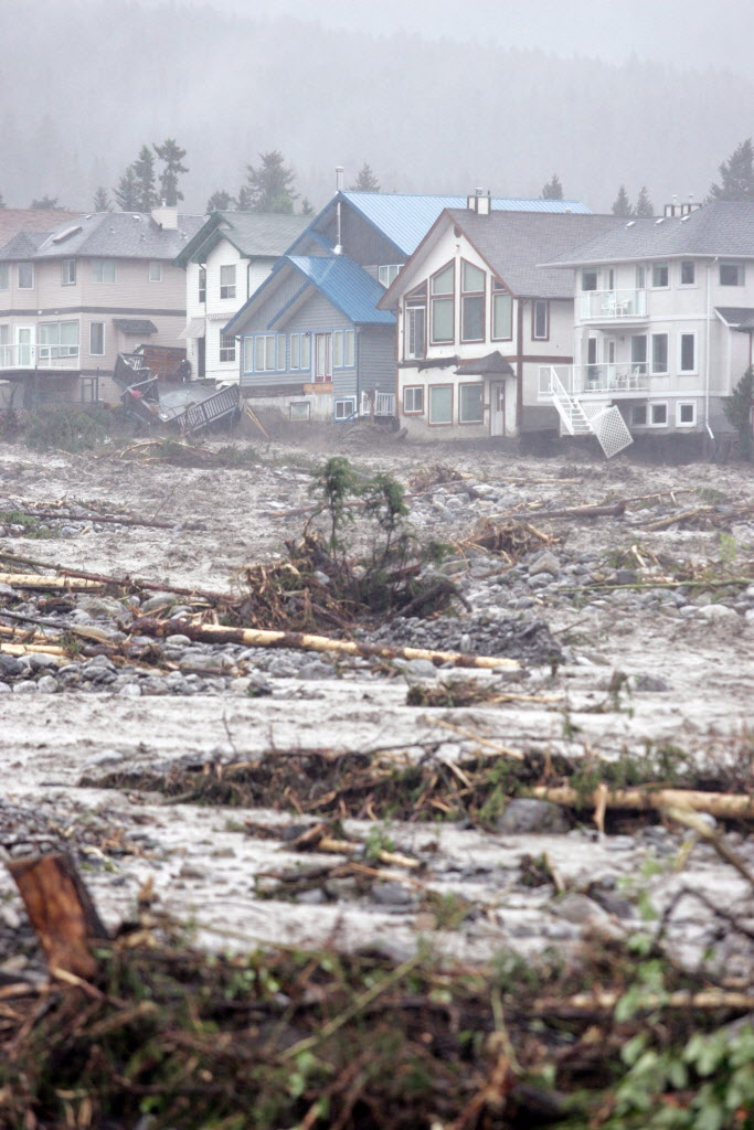Canmore homes along Cougar Creek barely hang on. (Craig Douce / The Canadian Press)