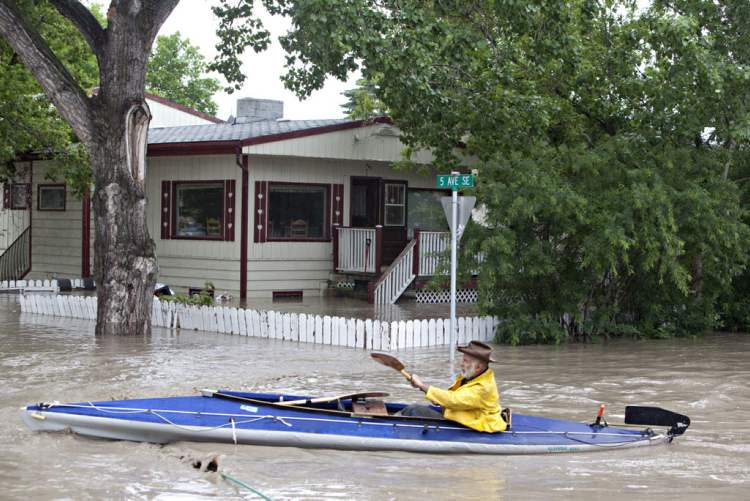 A kayaker paddles down a flooded street in High River, Alta. on June 20, 2013 after the Highwood River overflowed its banks.  (Jordan Verlage / The CAnadian press)
