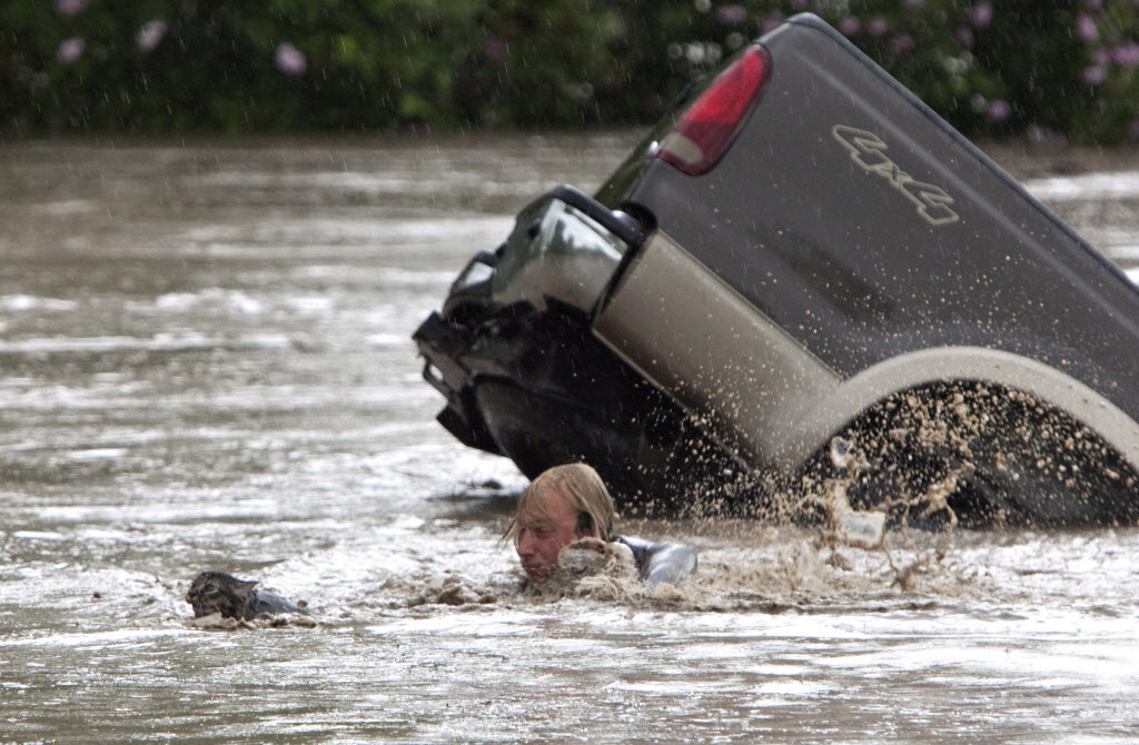 Kevan Yaets swims after his Momo to safety as his truck submerges. (JORDAN VERLAGE / The Canadian Press)