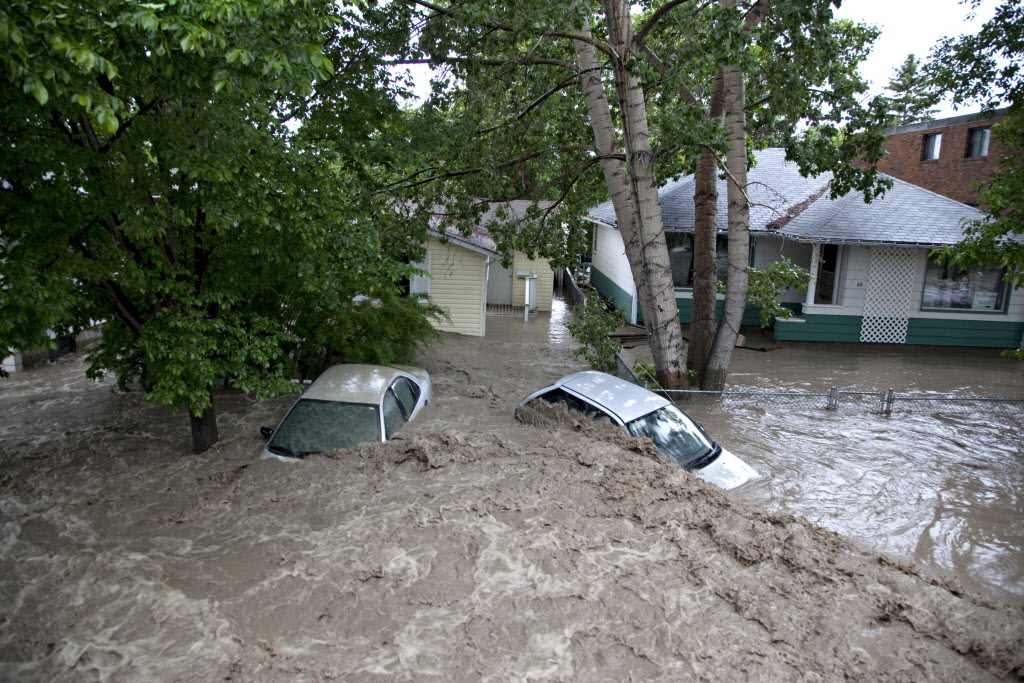 Submerged cars sit in the flood waters in High River, Alta. on June 20, 2013 after the Highwood River overflowed its banks.  Calgary and most of southern Alberta are being hammered by rain that has washed-out roads and bridges, caused mudslides and closed major highways.