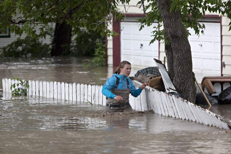 A woman wades through the flood waters in High River, Alta. (Jordan Verlage / The Canadian press)