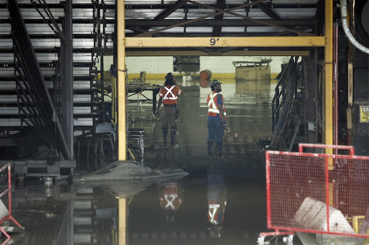 Clean-up crews venture inside the Saddledome Monday. (Jeff McIntosh / The Canadian Press)