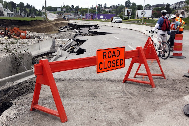 A cyclist and road crew survey the washed-out northbound lanes of MacLeod Trail in Calgary Monday. (Jeff McIntosh / The Canadian Press)
