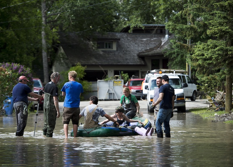 Bowness residents and volunteers take a break in a raft Monday. (Nathan Denette / The Canadian Press)