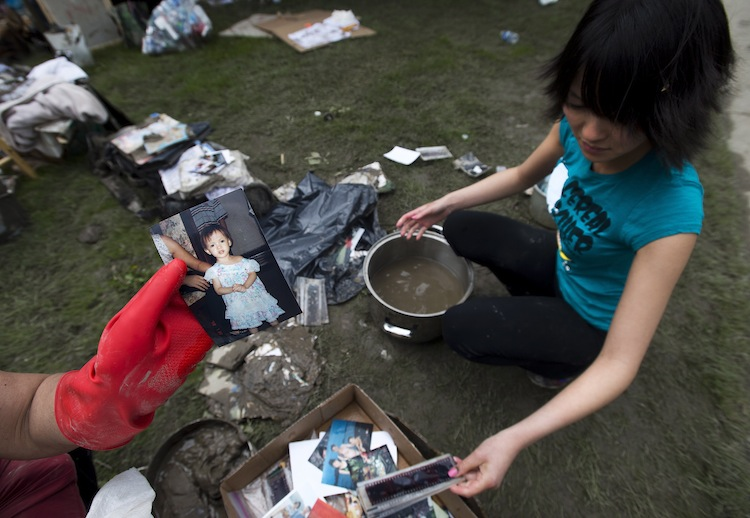 Resident Lisa Nguyen (right) cleans of the mud from photographs and negatives in Calgary Monday as volunteer Jacinta Babbitt shows a cleaned-up picture of Nguyen. (Nathan Denette / The Canadian Press)