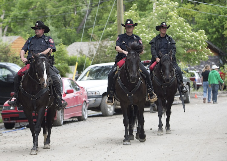 City of Calgary Police officers patrol the community of Bowness in Calgary on horseback Monday. (Nathan Denette / The Canadian Press)