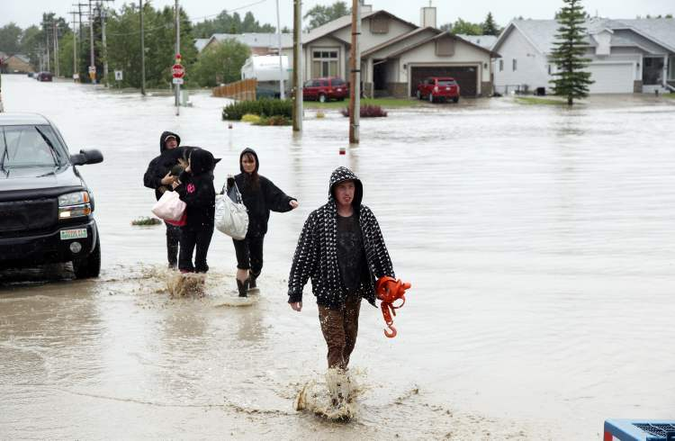 Residents wade through flood waters after an evacuation order in High River, Alta. (Jeff McIntosh / The Canadian Press)
