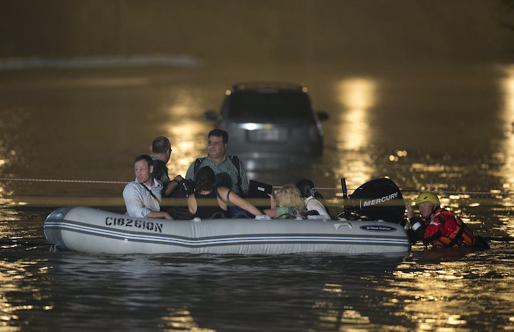 Stranded GO Train passengers make their way to dry land. (Frank Gunn / The Canadian Press)