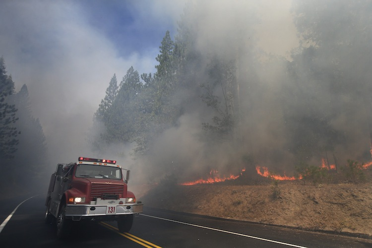 A fire truck drives past burning trees near Yosemite National Park, Calif., on Monday. (Jae C. Hong / The Associated Press)