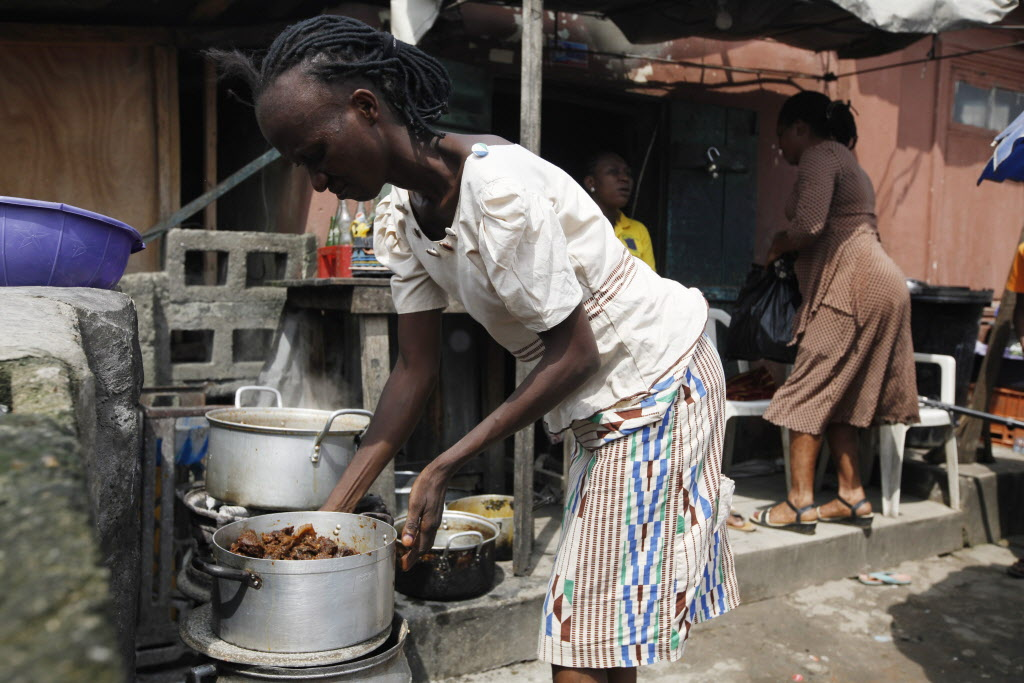 A woman prepares soup to sell on a street in Lagos, Nigeria, Thursday. (Sunday Alamba / The Associated Press )