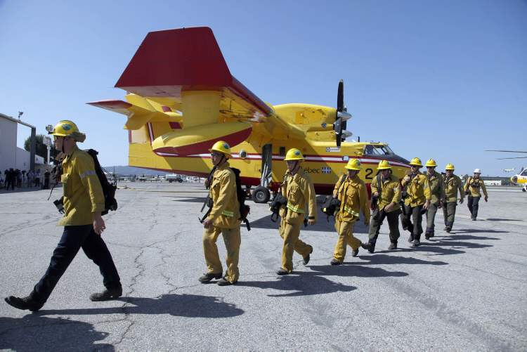 Los Angeles County firefighters walk past two Bombardier CL-415 Super Scooper firefighting planes parked at Van Nuys Airport in Los Angeles Monday. The aircraft, on lease from Quebec, arrived in Los Angeles County to bolster the fire department's efforts against wildfires.