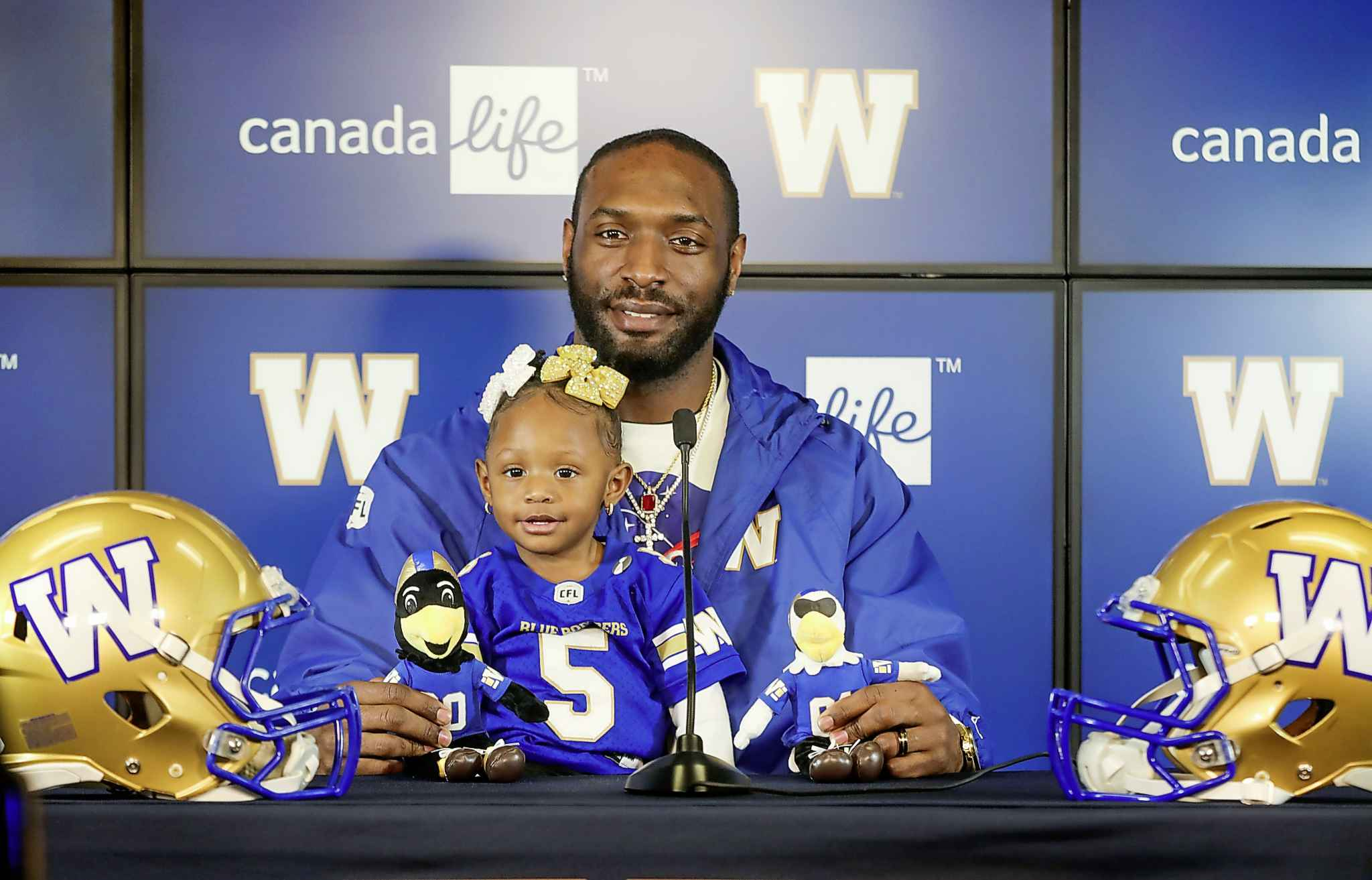 Blue Bombers' Willie Jefferson, with his daughter 22-month-old Kelley, answers questions from the media about signing on with the Bombers for another 2 seasons on Thursday.