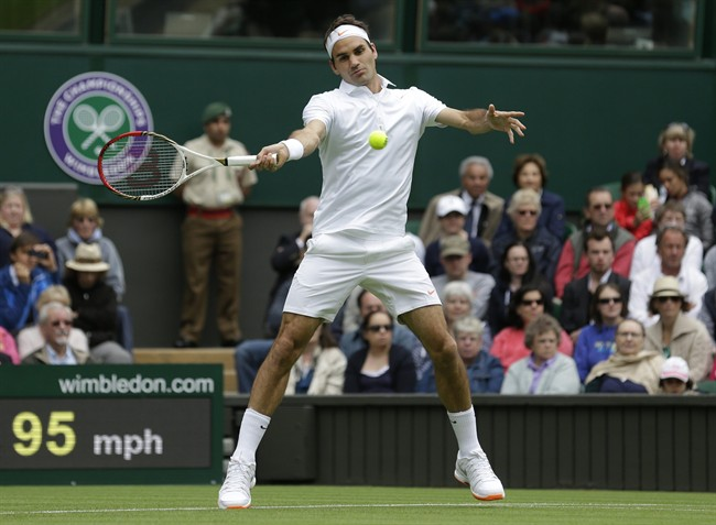 Roger Federer of Switzerland returns the ball to Victor Hanescu of Romania during their Men's first round singles match at the All England Lawn Tennis Championships in Wimbledon, London, Monday, June 24, 2013. (AP Photo/Anja Niedringhaus)