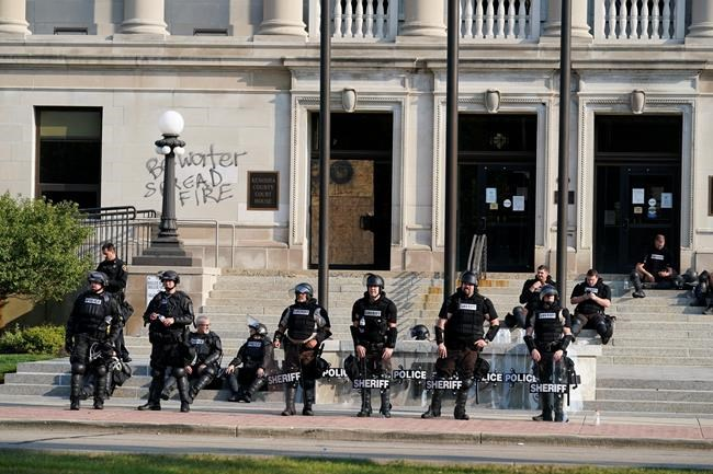 Police in riot gear stand outside the Kenosha County Court House Monday, Aug. 24, 2020, in Kenosha, Wis. Kenosha police shot a man Sunday evening, setting off unrest in the city after a video appeared to show the officer firing several shots at close range into the man's back. (AP Photo/Morry Gash)