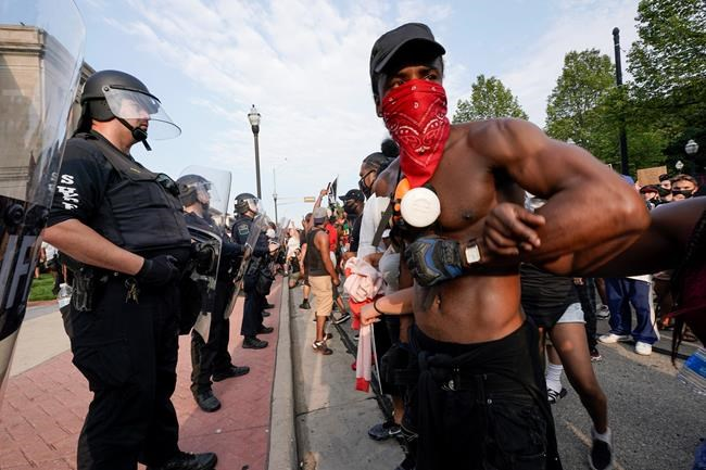Protesters link arms in front of a police line outside the Kenosha County courthouse Monday, Aug. 24, 2020, in Kenosha, Wis. Wisconsin Gov. Tony Evers has summoned the National Guard to head off another round of violent protests after the police shooting of a Black man turned Kenosha into the nation's latest flashpoint city in a summer of racial unrest. (AP Photo/Morry Gash)