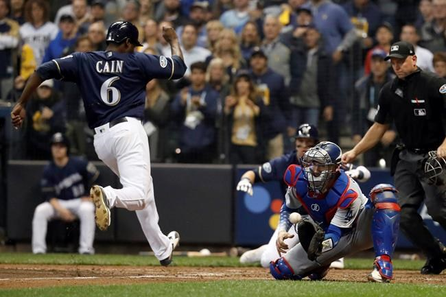 Milwaukee Brewers' Lorenzo Cain (6) scores a run as Los Angeles Dodgers catcher Yasmani Grandal misses a tag during the third inning of Game 1 of the National League Championship Series baseball game Friday, Oct. 12, 2018, in Milwaukee. (AP Photo/Jeff Roberson)