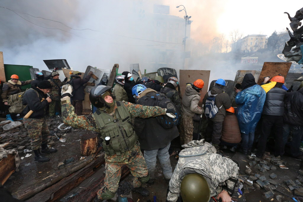 A protester hurls a cobblestone over a wall of fire toward police forces storming Independence Square in central Kyiv on Wednesday.