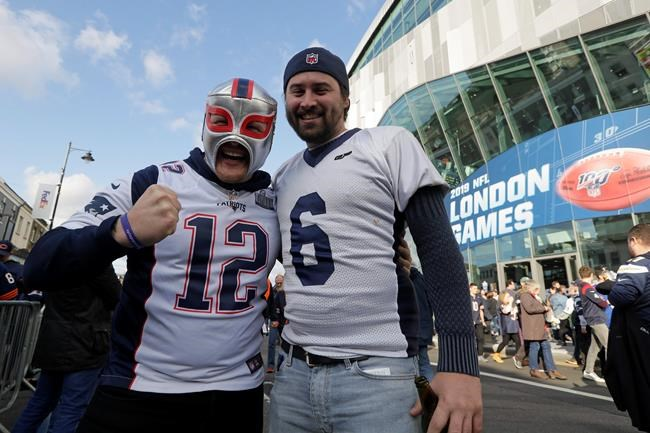 CORRECTS STADIUM TO TOTTENHAM HOTSPUR STADIUM INSTEAD OF WEMBLEY STADIUM - Fans waits to enter Tottenham Hotspur Stadium before an NFL football game between the Chicago Bears and the Oakland Raiders, Sunday, Oct. 6, 2019, in London. (AP Photo/Kirsty Wigglesworth)