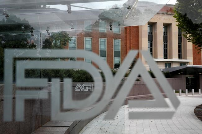 "FILE - This Aug. 2, 2018, file photo shows the U.S. Food and Drug Administration building behind FDA logos at a bus stop on the agency's campus in Silver Spring, Md. In a report to Congress and an accompanying ""playbook"" for states and localities, key federal health agencies and the Defense Department sketched out complex plans for a vaccination campaign to begin gradually early next year or later in 2020, eventually ramping up to reach any American who wants a shot. The Pentagon is involved with the distribution of vaccines, but civilian health workers will be the ones giving shots. (AP Photo/Jacquelyn Martin, File)"