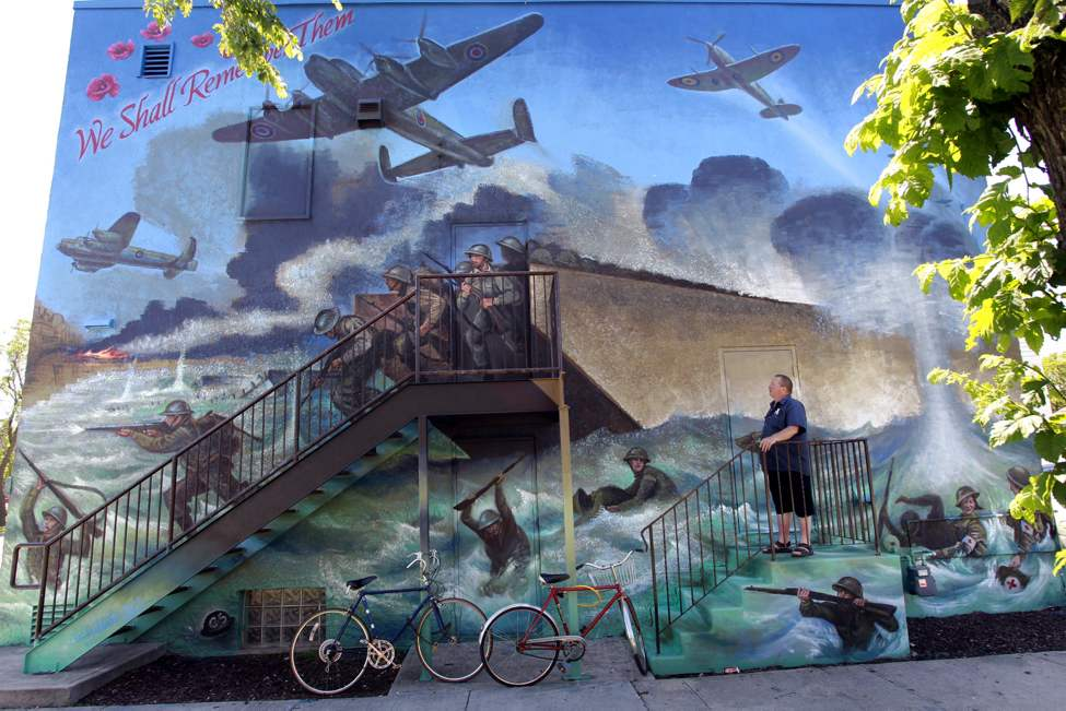 Neil Klassen, member and House and Building Manager of the Royal Canadian Legion, West Kildonan BR. 30 beside the mural titled