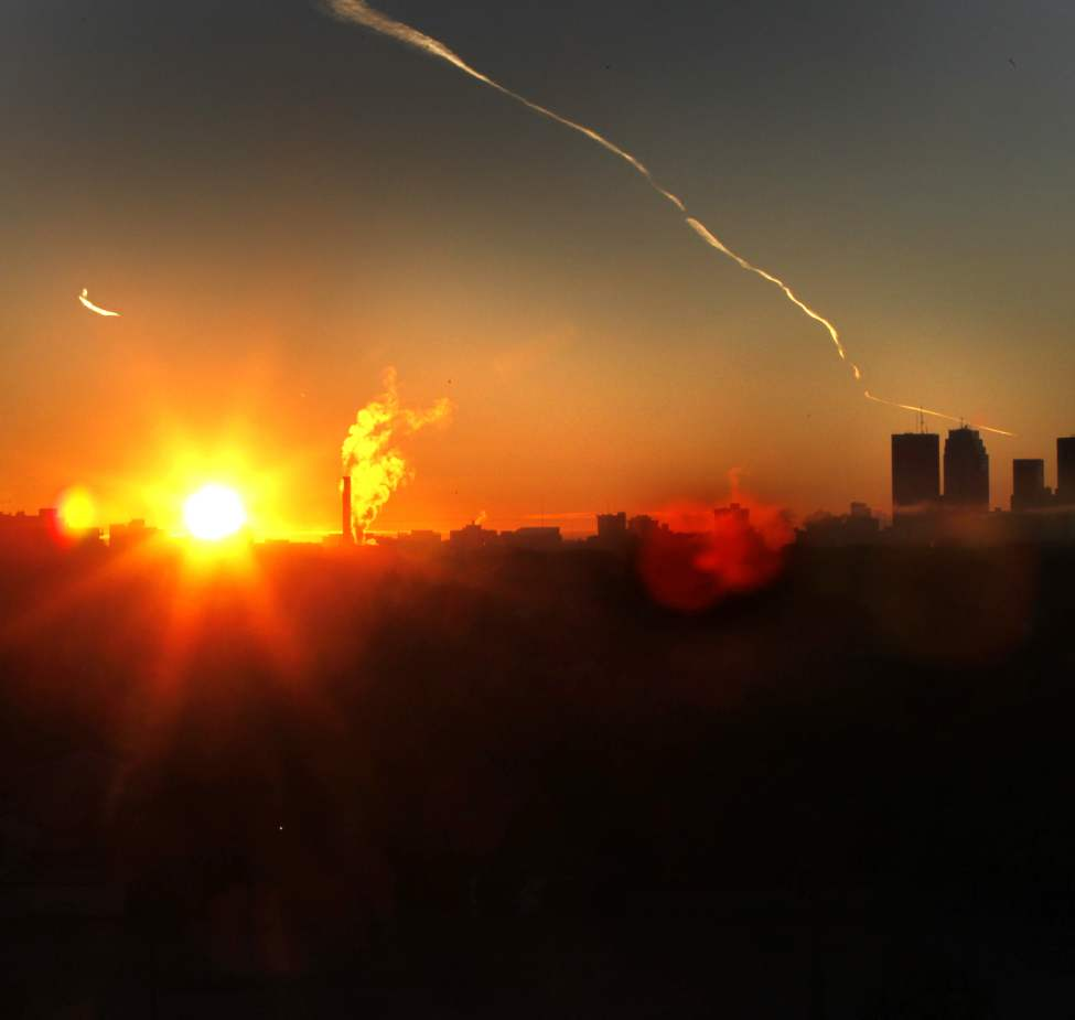 The warm glow of the sunrise illuminates Winnipeg's downtown.