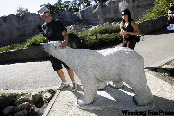 Riley Sawka and Kylie Newman check out a statue of Debby Thursday at the Assiniboine Park Zoo. Debby died in 2008 as the oldest polar bear in captivity.