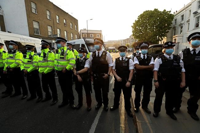A police line stands outside Stamford Bridge stadium in London where Chelsea fans were protesting against Chelsea's decision to be included amongst the clubs attempting to form a new European Super League, Tuesday, April 20, 2021. Reaction to the proposals from 12 clubs to rip up European soccer by forming a breakaway Super League has ranged from anger and condemnation to humor and sarcasm. (AP Photo/Matt Dunham)