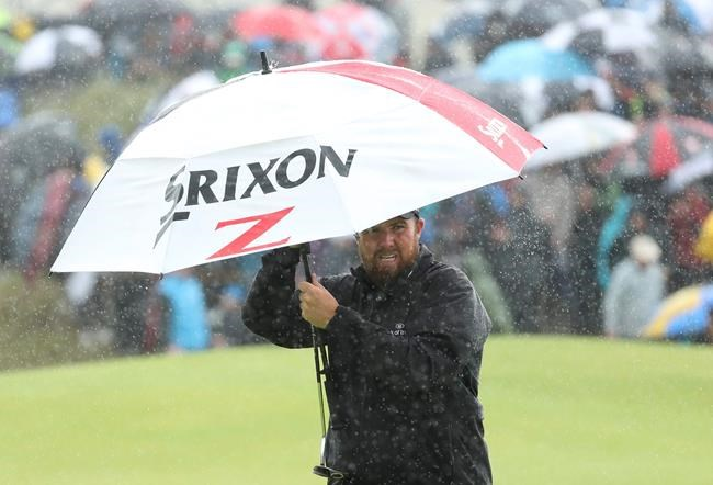Ireland's Shane Lowry holds an umbrella in heaven rain on the 8th green during the final round of the British Open Golf Championships at Royal Portrush in Northern Ireland, Sunday, July 21, 2019.(AP Photo/Peter Morrison)