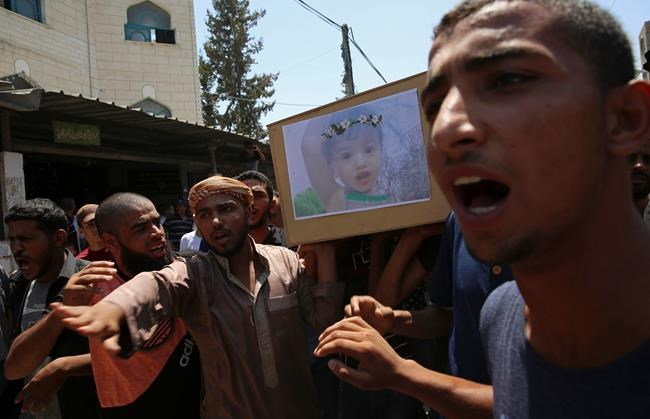 Palestinian mourners chants Islamic slogans while carrying the coffin of 23-year-old pregnant mother Enas Khamash and her daughter Bayan, whose picture is on the coffin, during their funeral in Deir el-Balah, central Gaza Strip, Thursday, Aug. 9, 2018. Israeli warplanes have hit dozens of targets in the Gaza Strip, while Palestinian militants fired scores of rockets into Israel in a fierce burst of violence overnight. At least three Palestinians, including Khamash and her daughter, were reported killed and seven people were wounded on the Israeli side. (AP Photo/Adel Hana)