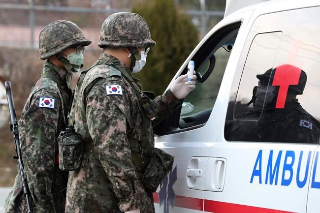 South Korean army soldiers wearing face masks check the temperature of a driver at a checkpoint of a military base in Daegu, South Korea, Wednesday, Feb. 26, 2020. The number of new virus infections in South Korea jumped again Wednesday and the U.S. military reported its first case among its soldiers based in the Asian country, with his case and many others connected to a southeastern city with an illness cluster. (Ryu Hyung-seok/Yonhap via AP)