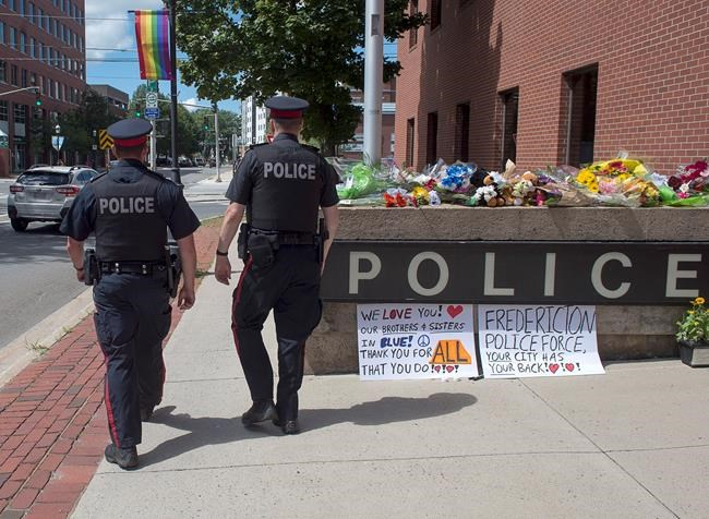 Two officers walk past an array of flowers outside the police station in Fredericton on Friday, Aug. 10, 2018. Two city officers were among four people who died in a shooting in a residential area on the city's north side.THE CANADIAN PRESS/Andrew Vaughan