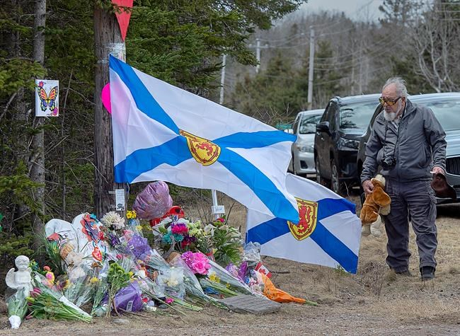A man pays his respects at a roadside memorial in Portapique, N.S. on Thursday, April 23, 2020. RCMP say at least 22 people are dead after a man who at one point wore a police uniform and drove a mock-up cruiser, went on a murder rampage in Portapique and several other Nova Scotia communities. THE CANADIAN PRESS/Andrew Vaughan