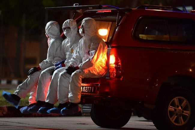 In this photo taken and released by Malaysia's Ministry of Health, health workers wearing full protective suits sit on a vehicle as they wait for the arrival of evacuated Malaysian from China's Wuhan, the epicenter of the coronavirus outbreak, at Kuala Lumpur International Airport in Sepang, Malaysia, Wednesday, Feb. 26, 2020. U.S. health officials warned Tuesday that the burgeoning coronavirus is certain to spread more widely in the country at some point, even as their counterparts in Europe and Asia scrambled to contain new outbreaks of the illness. (Muzzafar Kasim/Malaysia's Ministry of Health via AP)