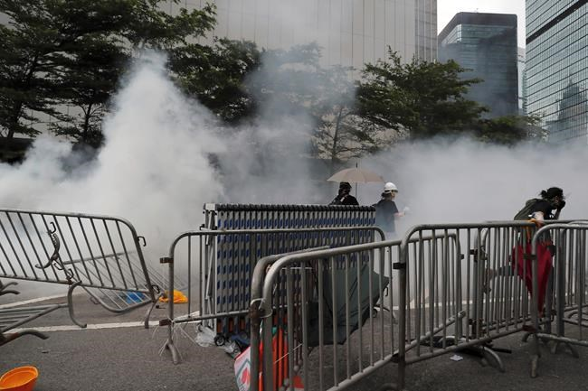 Protesters run away from the tear gas fired by police during a rally outside the Legislative Council in Hong Kong, Wednesday, June 12, 2019. Hong Kong delayed a legislative session on a contentious extradition bill as thousands of protesters amassed to block entry to the building Wednesday out of concern the measure signaled greater Chinese control and further erosion of civil liberties in the semiautonomous territory. (AP Photo/Kin Cheung)