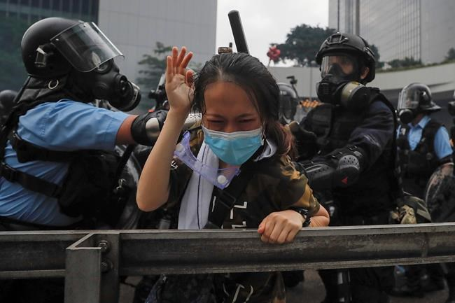A protester reacts as she tackled by riot police during a massive demonstration outside the Legislative Council in Hong Kong, Wednesday, June 12, 2019. Hong Kong police have used tear gas and high-pressure hoses against thousands of protesters opposing a highly controversial extradition bill outside government headquarters. (AP Photo/Kin Cheung)