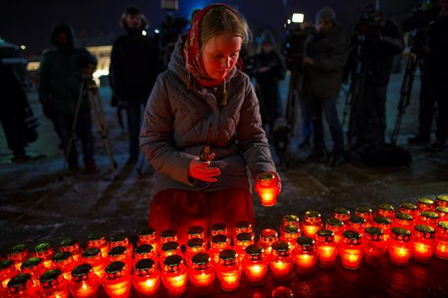 A girl places a candle as a group gather at the Cathedral of Christ the Savior in Moscow to light 71 candles in memory of those killed in the An-148 plane crash, on Monday, Feb. 12, 2018. A Russian passenger plane carrying 71 people crashed Sunday near Moscow, killing everyone aboard shortly after the jet took off from one of the city's airports. The Saratov Airlines regional jet disappeared from radar screens a few minutes after departing from Domodedovo Airport en route to Orsk, a city some 1,500 kilometers (1,000 miles) southeast of Moscow. (AP Photo/Alexander Zemlianichenko)