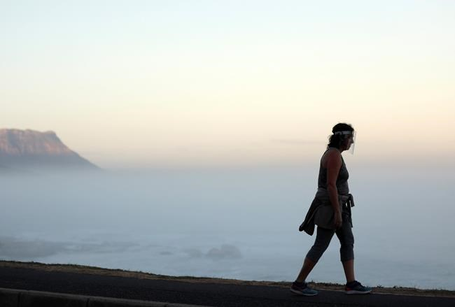 A woman wearing a face shield walks along the road in Clifton, Cape Town, South Africa, Friday, May 22, 2020. Cape Town has become the center of the COVID-19 outbreak in South Africa and one of Africa's hot spots. The province containing Johannesburg, South Africa's largest city, and the capital, Pretoria, had been expected to be the country's epicenter with its population density and poverty levels but Cape Town defied predictions with high levels of community transmission. (AP Photo/Nardus Engelbrecht)