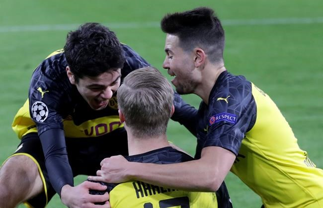 Dortmund's Erling Braut Haaland, center, celebrates with teammates after scoring his side's opening goal during the Champions League round of 16 first leg soccer match between Borussia Dortmund and Paris Saint Germain in Dortmund, Germany, Tuesday, Feb. 18, 2020. (AP Photo/Michael Probst)